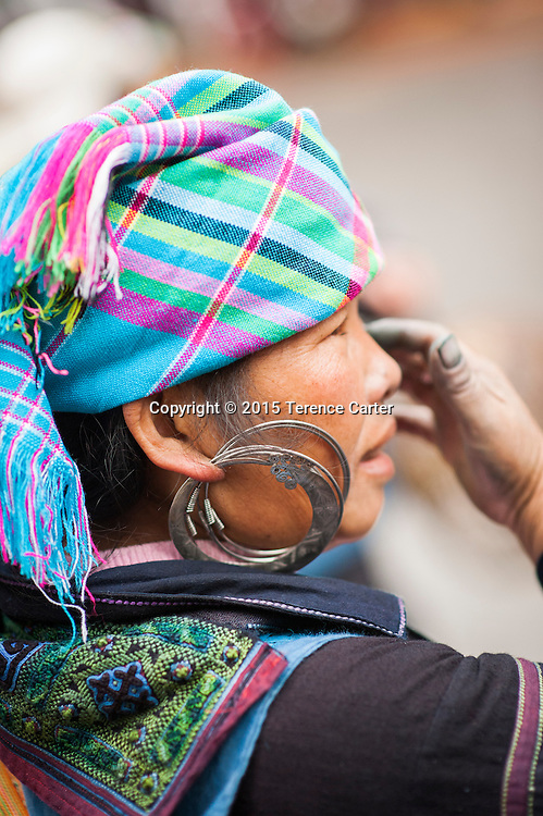 A hilltribe woman wears a distictive scarf and earrings in the markets in Sapa, Vietnam.