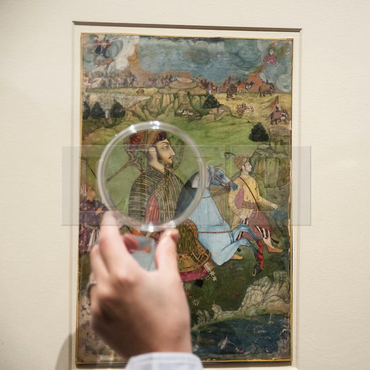 "© Licensed to London News Pictures. 02/10/2015. London, UK. A visitor uses a magnifying glass to view ""A prince holding a falcon and galloping through a rocky landscape, Deccan, Golconda"" (est. £60k - 80k), a highlight from the Sven Gahlin Collection of 157 finely painted Indian miniature paintings at the preview of Indian and Islamic Art Week at Sotheby's which runs from 2 to 7 October.   Photo credit : Stephen Chung/LNP"