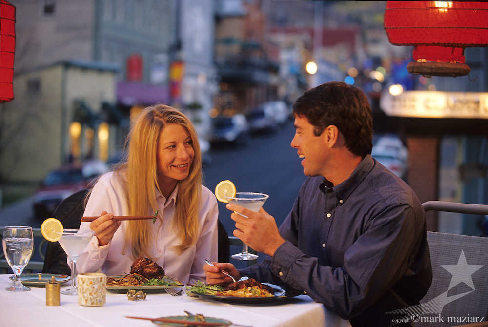 Couple dining on deck over Main Street, Park City, Utah.