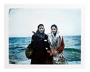 Two young refugee women posing for a portrait soon after their arrival on Lesvos Island. The girl on the right is still wearing the emergency blanket given to her after reaching the shore to keep her body temperature stable.<br /> Skala, Lesvos, Greece, January 2016.<br /> <br /> I asked the subjects to pose but I did not direct the scene. The subjects decided where and how to pose. <br /> <br /> The original picture is a Polaroid Fujifilm FP-100C, which I re-photographed with Nikon 800 in my studio. Polaroid Camera: Polaroid 30 and Polaroid 103. The original picture can be provided upon request.