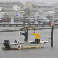 Brian Mattice (C) and Charlie Harrison secure a floating dock  in Cedar Key, Florda in preparation for Tropical Storm Alberto as television trucks line the background June12, 2006. REUTERS/Scott Audette