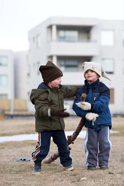 Ari Carl og Benedikt leika sér með trjágrein sem þeir fundu úti á túni.
