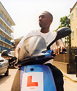 Teenage boy with L plates on his scooter sitting outside a housing estate