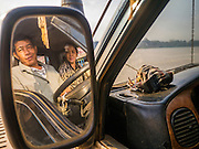 11 MARCH 2013 - ALONG HIGHWAY 13, LAOS: A truck driver and his wife sit in the cab of their truck on a Mekong River ferry. The Mekong River ferries are disappearing as bridges across the river are completed and roads along the river are paved. The paving of Highway 13 from Vientiane to near the Chinese border has changed the way of life in rural Laos. Villagers near Luang Prabang used to have to take unreliable boats that took three hours round trip to get from the homes to the tourist center of Luang Prabang, now they take a 40 minute round trip bus ride. North of Luang Prabang, paving the highway has been an opportunity for China to use Laos as a transshipping point. Chinese merchandise now goes through Laos to Thailand where it's put on Thai trains and taken to the deep water port east of Bangkok. The Chinese have also expanded their economic empire into Laos. Chinese hotels and businesses are common in northern Laos and in some cities, like Oudomxay, are now up to 40% percent. As the roads are paved, more people move away from their traditional homes in the mountains of Laos and crowd the side of the road living off tourists' and truck drivers.    PHOTO BY JACK KURTZ