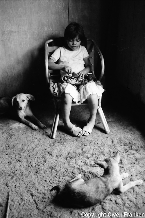 Nicaragua, child eating near her dogs