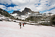 Hiking across a snow field above Garnet Lake with Banner and Ritter peaks in the background. High Sierra backpacking trip to Garnet Lake and Nydiver Lake in the Ansel Adams Wilderness out of Devil's Postpile national monument 2017.