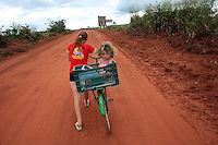 A young girl gets a ride in a bicycle basket just outside of Marcelândia, in Mato Grosso state, in Brazil on April 5, 2008. (Photo/Scott Dalton).