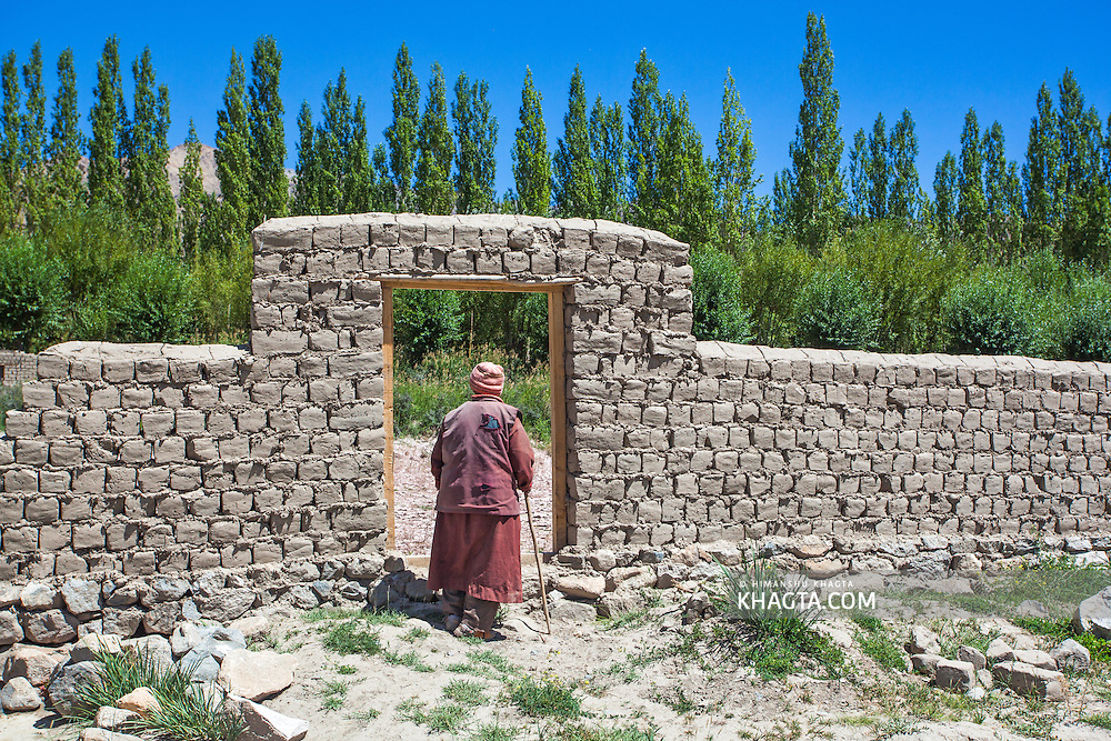 A lady  stands by the door on a mud wall in Thiksey, Ladakh