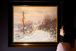 © Licensed to London News Pictures. 01/02/2012. LONDON, UK. A member of Sotherby's looks at Claude Monet's 'L'entree de Giverny en hiver' ahead of an auction of Impressionist and Modern Art held on the 8th of February 2012. The previously unseen piece is estimated to raise £4,500,000-6,500,000. Photo credit: Matt Cetti-Roberts/LNP