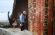 TIJUANA, MEX-FEB 22:  A man walks along the U.S.-Mexico border wall in Tijuana, Mexico on Sunday, February 22, 2015.   Senior Republican senators said they expected Congress will avoid a shutdown over the Department of Homeland Security, which faces a partial shutdown on Feb. 27 over a GOP push to roll back President Barack Obama's executive actions on immigration.(Photo by Sandy Huffaker/Getty Images)