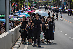 October 14, 2016 - Bangkok, Bangkok, Thailand - Thai Royalists and well-wishers walks along the road outside Siriraj Hospital to await the funeral procession of Thailand's King Bhumibol Adulyadej in Bangkok, Thailand on October 14, 2016. Thai King Bhumibol Adulyadej was the world's longest reigning monarch and died at the age of 88 after a long illness since several years, he was the most unifying symbol for Thai people and leaving behind him a divided country under military control. Prime Minister Prayut Chan-o-Cha made a statement that Thailand would have one year period of mourning for HM the King. (Credit Image: © Guillaume Payen/NurPhoto via ZUMA Press)