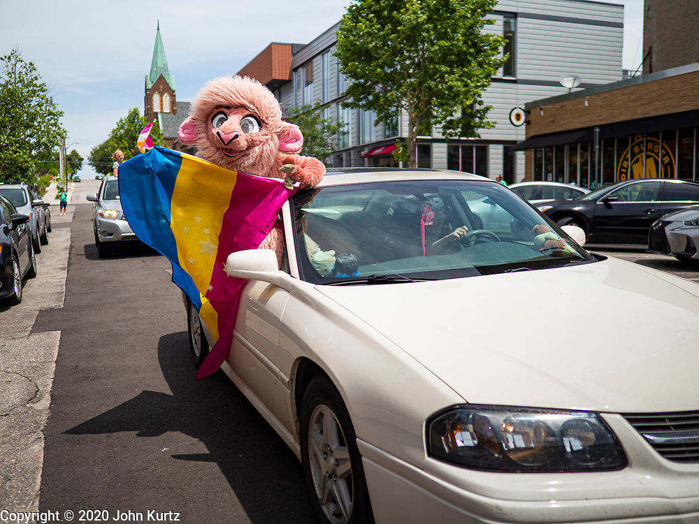 "28 JUNE 2020 - DES MOINES, IOWA: A participant in the Capitol City Pride Parade in Des Moines. Most of the Pride Month events in Des Moines were cancelled this year because of the COVID-19 pandemic, but members of the Des Moines LGBTQI community, and Capitol City Pride, the organization that coordinates Pride Month events, organized a community ""parade"" of people driving through the East Village of Des Moines displaying gay pride banners and flags. About 75 cars participated in the parade.     PHOTO BY JACK KURTZ"