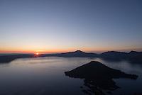 The sun rises over the rim of Crater Lake, Oregon