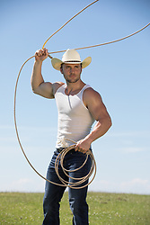 hot cowboy working with a lasso on a ranch