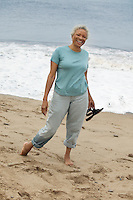 Smiling Woman Walking Barefoot on Beach