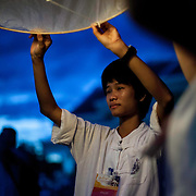 Western tourist and others gather Saturday, Nov. 16, 2013, near Mae Jo University in Chiang Mai, Thailand to listen to prayers and await the launch of sky lanterns as part of local celebrations of Yi Peng.  The religious ceremony is held to pay homage to Buddha. Yi Peng coincides with  Loi Krathong a religious holiday celebrated throughout Thailand.  (photo by/ David Longstreath)