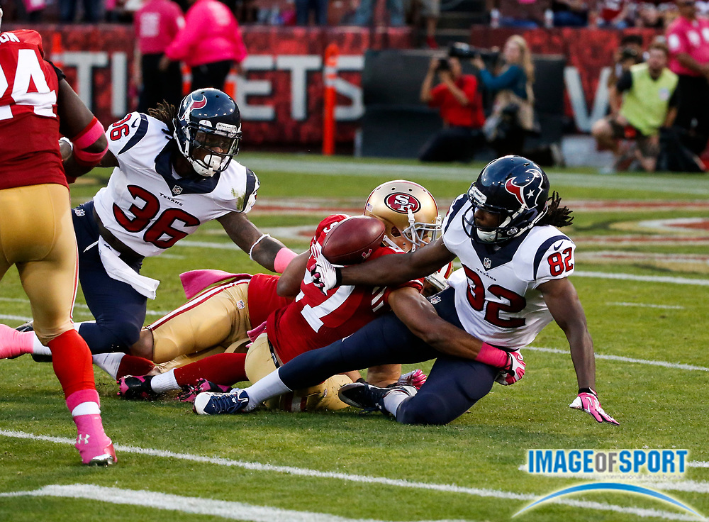 Oct 6, 2013; San Francisco, CA, USA;  Houston Texans wide receiver Keshawn Martin (82) bobbles the ball after a 16-yard kickoff return as he is tackled by San Francisco 49ers safety C.J. Spillman (27) at Candlestick Park. The 49ers defeated the Texans 34-3.