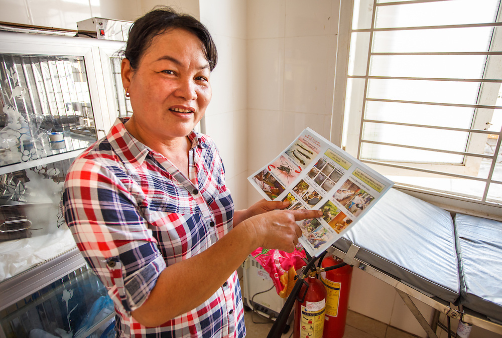 CAPTION: Healthcare practitioner Thuong Thi My Dung holds a leaflet which shows measures households can take to prevent dengue fever outbreaks. The leaflets, along with posters and other educational materials, are distributed in local communities to raise awareness of dengue fever prevention measures. LOCATION: Long Tuyen Health Centre, Can Tho, Vietnam. INDIVIDUAL(S) PHOTOGRAPHED: Thuong Thi My Dung.