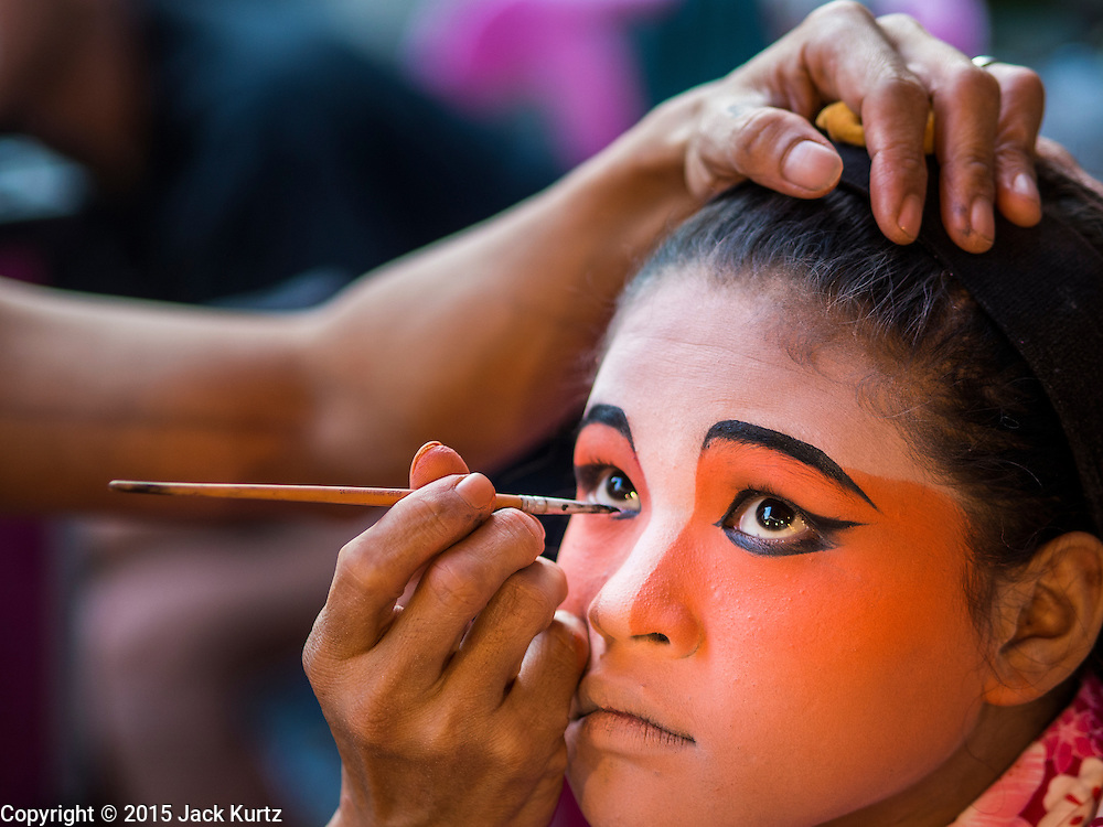 16 JANUARY 2015 - BANGKOK, THAILAND: Performers with Sai Yong Hong Teochew Opera Troupe put on their make up before performing at the Chaomae Thapthim Shrine, a Chinese shrine in a working class neighborhood of Bangkok near the Chulalongkorn University campus. The troupe's nine night performance at the shrine is an annual tradition and is the start of the Lunar New Year celebrations in the neighborhood. Lunar New Year, also called Chinese New Year, is officially February 19 this year. Teochew opera is a form of Chinese opera that is popular in Thailand and Malaysia.    PHOTO BY JACK KURTZ