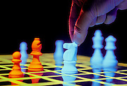 Hand moving a glowing chess piece on a black light reactive chess board.Black light