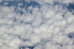 Aerial photograph of cotton ball like clouds from an airplane window.