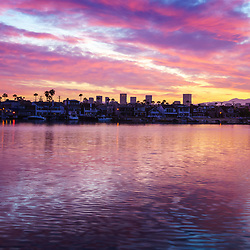 Newport Beach California skyline sunrise photo with Fashion Island office buildings, Balboa Island homes, and Newport Harbor. Newport Beach is an affluent beach city in Orange County Southern California in the United States of America. Photo is high resolution. Copyright ⓒ 2017 Paul Velgos with All Rights Reserved.