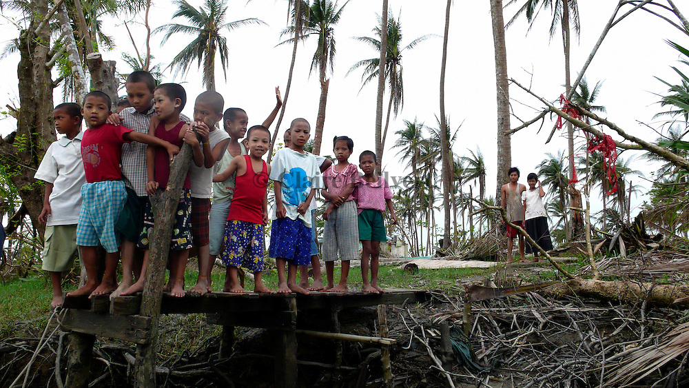 Children waiting for the boat of Burmese donators from Rangoon who are bringing some rice and sweets to the villagers of the Delta, Myanmar.  In the aftermath of Cyclone Nargis, these villagers desperately need food aid as their rice stocks have been destroyed by the cyclone.