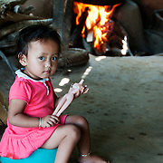 Nepal 2014. Pangma village. Paralisa sits on her potty with a broken barbie doll.