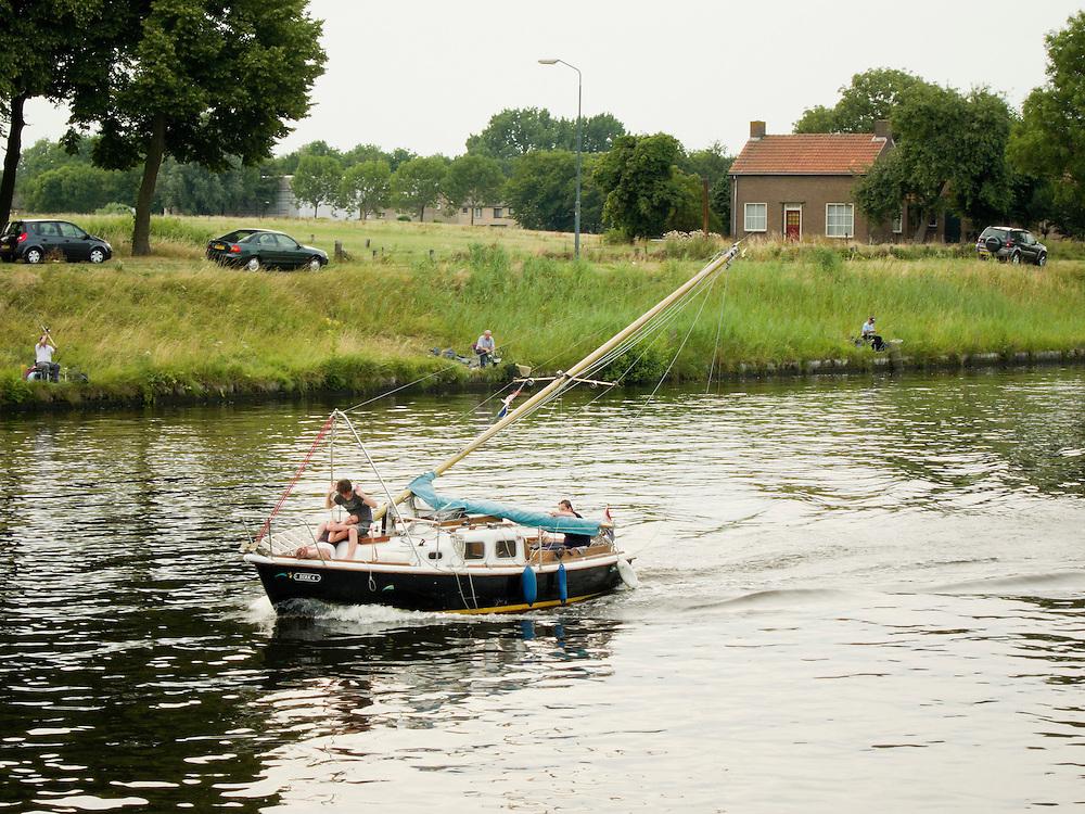 Nederland, Den Bosch, 20100720..Gezicht op Engelen vanaf de rivier de Dieze. Hengelaars langs de waterkant. Een zeilbootje met neergelaten mast vaart voorbij.    .Gerlo Beernink/Hollandse Hoogte