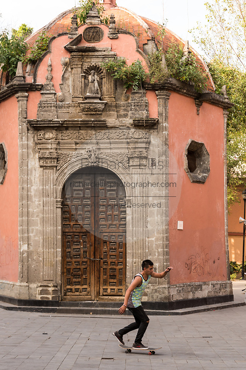 A young boy on a skateboard passes the tiny Baroque style Chapel of la Concepción Cuepopan also know as the La Conchita or the Chapel of the Dead in the Concepcion Square of Mexico City, Mexico.