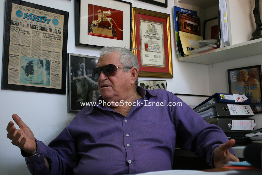 Israeli producer and director Menahem Golan is looking at his many awards, hanging on his office wall  in Tel-Aviv. .