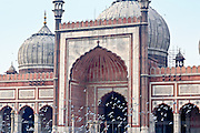 INDIA, OLD DELHI:  Exterior of Jama Masjid Mosque in Old Delhi with a flock of pigeons flying by the arched entrance.