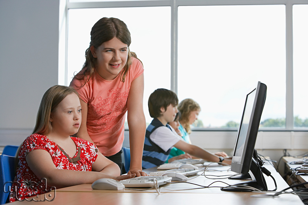 Two girls (10-12) using computer in computer lab children in background