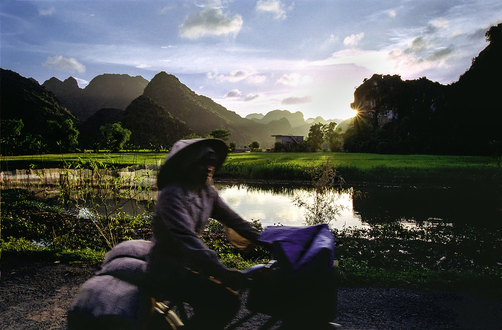 A woman wearing a traditional vietnamese hat passes by on her bicycle as the sun set over the rice fields and limestone mountains of Tam Coc, near the city of Nimh Binh, a couple hours south of Hanoi, Vietnam, 2003.