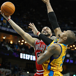 February 12, 2011; New Orleans, LA, USA; Chicago Bulls power forward Carlos Boozer (5) shoots over New Orleans Hornets power forward David West (30) during the fourth quarter at the New Orleans Arena.  The Bulls defeated the Hornets 97-88. Mandatory Credit: Derick E. Hingle