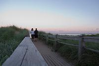 Two women walk the boardwalk at sunset at Basin Head beach, Prince Edward Island, Canada.