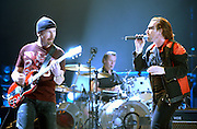 From left; The Edge, Larry Muellen, and Bono of the rock group U2 perform in Salt Lake City, Utah. Photo by Colin E Braley
