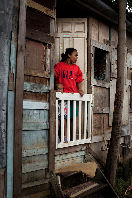 A woman in her barrack in the risk area of the favela. The barracks are on the slope of a hill.  Favela São Rafael, Guarulhos, Brazil.