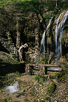 GARDONE RIVIERA, ITALY - 20 APRIL 2018: A bronze statue of Aphrodite is seen here by the stream of Crazy Water which then flows downstream into the valley, at the Vittoriale degli Italiani, a hillside estate overlooking the Garda lake and  where the Italian writer Gabriele d'Annunzio lived after his defenestration in 1922 until his death in 1938, in Gardone Riviera, Italy, on April 20th 2018.<br /> <br /> Lake Garda is the largest lake in Italy. It is a popular holiday location located in northern Italy, about halfway between Brescia and Verona, and between Venice and Milan on the edge of the Dolomites. The lake and its shoreline are divided between the provinces of Verona (to the south-east), Brescia (south-west), and Trentino (north).