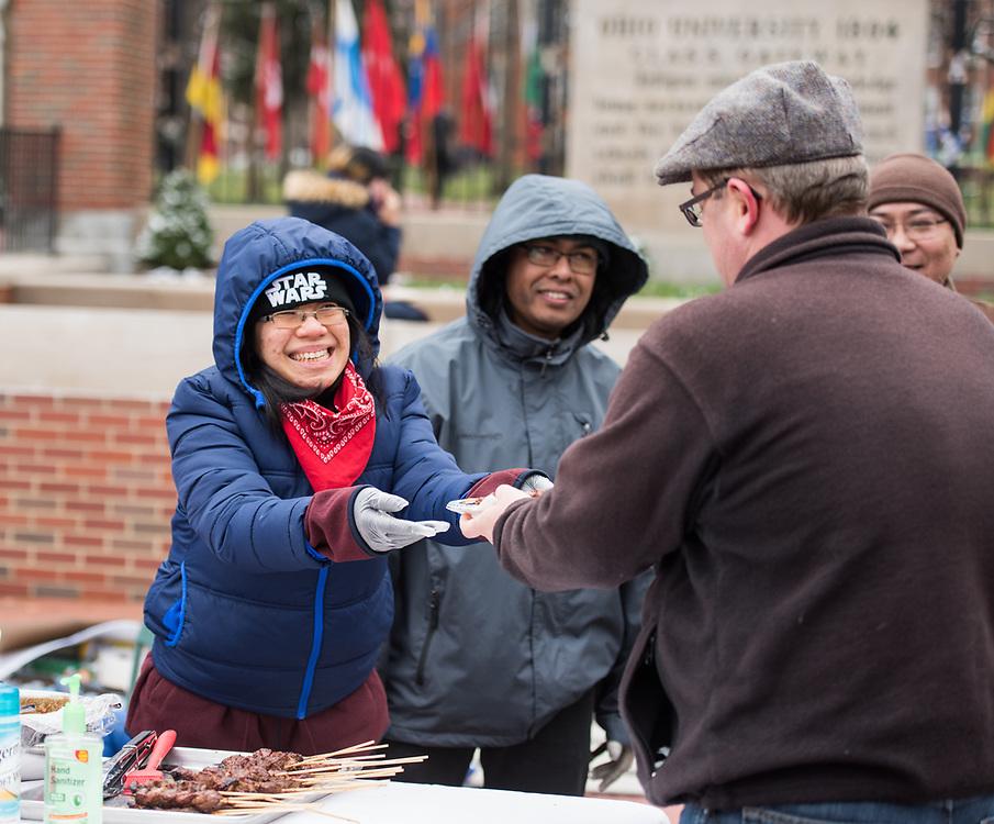 Inda, a community member from Indonesia, hands a plate of  Lamb Satay to Ohio University faculty member Benjamin Bates.