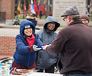 Inda, a community member from Indonesia, hands a plate of  Lamb Satay to Ohio University faculty member Benjamin Bates.