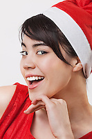 Close-up portrait of cheerful woman wearing Santa Claus hat over white background
