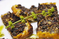 Pesto Bruschetta  with Tepenade, a basil sprig on top
