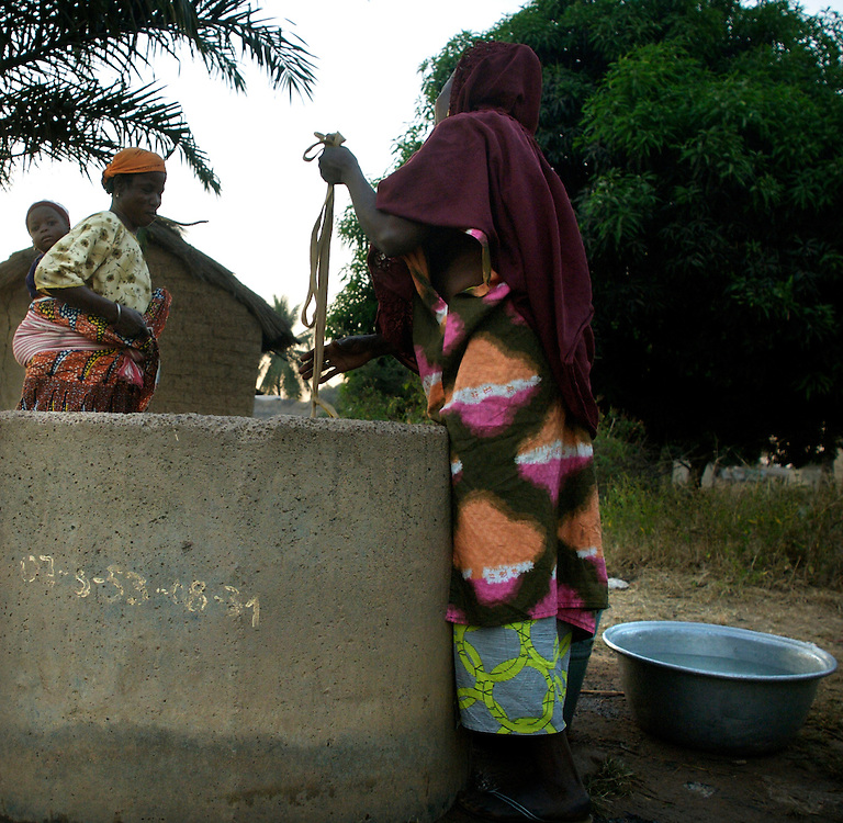 Djougou November 2006 - A group of women fill water in a jerrycan by using a water well. © Jean-Michel Clajot