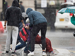 © Licensed to London News Pictures. 26/09/2019. London, UK. A member of the public is helped back to their feet by passers by after sipping in wet conditions in Parliament Square, Westminster, London. The UK has been deluged with rain causing flash floods in parts. Photo credit: Peter Macdiarmid/LNP