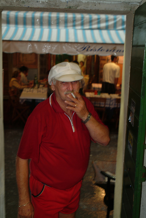 Old man smoking cigarette outside of store in Monterrosso, Cinque Terre, Italy