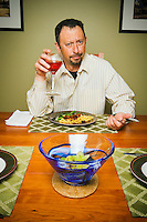 Portrait of skeptical man drinking wine and eating dinner.