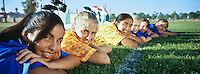 Teenage girls (13-16) lying in row on soccer field