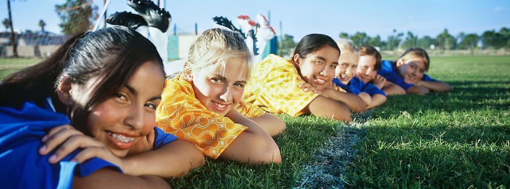 Teenage girls (13-16) lying in row on soccer field