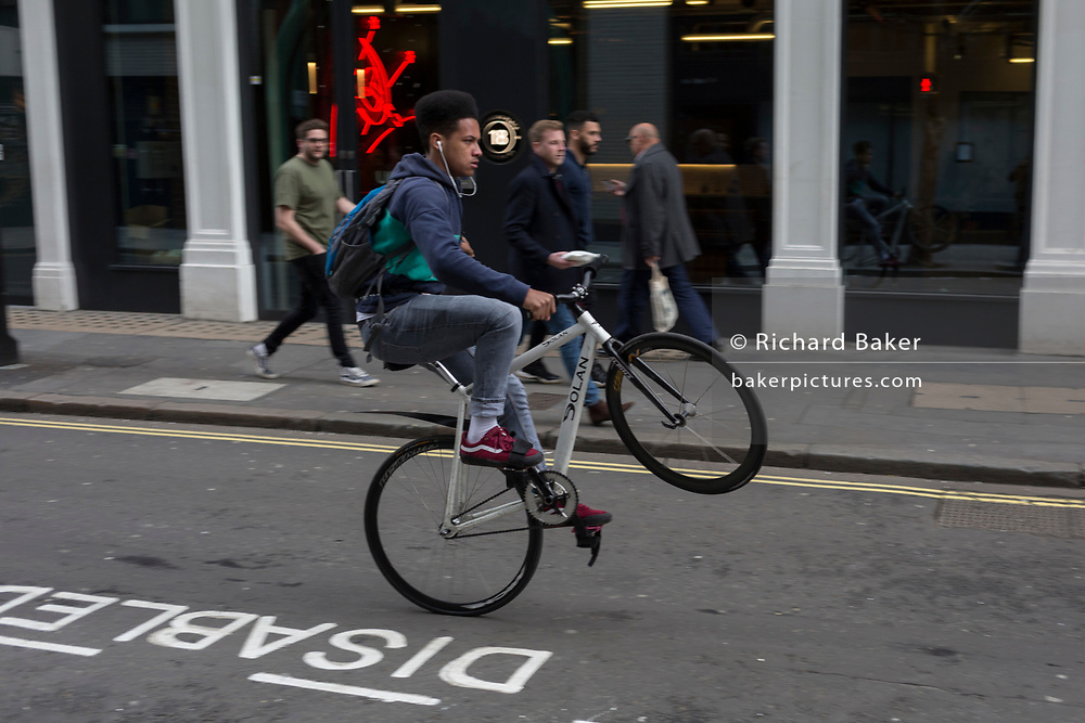 A young man wheelies his bike in a West End street, on 4th March 2019, in London England.